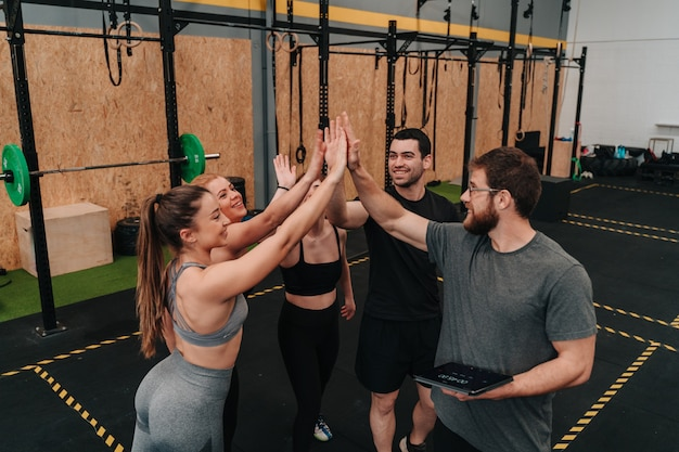Grupa młodych sportowców na siłowni crossfit, szczęśliwych po treningu jako zespół dla ich dobrego samopoczucia.