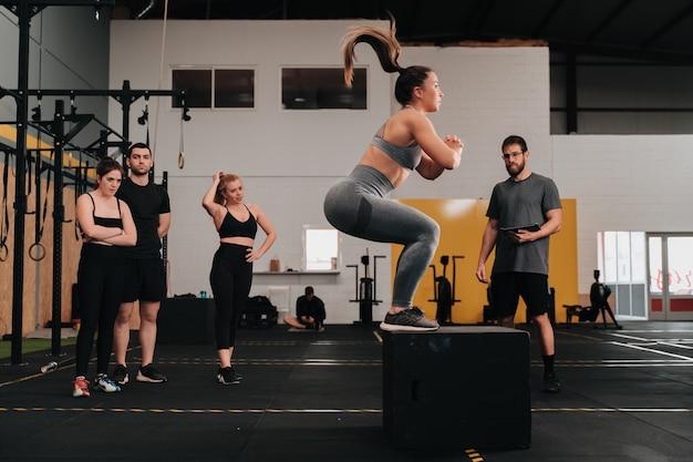 Grupa młodych sportowców na siłowni crossfit wykonujących różnorodne ćwiczenia, podczas gdy trener i inni członkowie grupy kibicują im