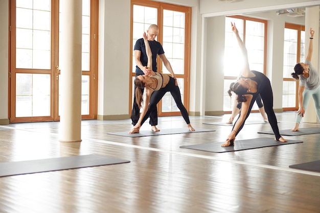 Grupa młodych sportowców praktykujących lekcję jogi z instruktorem. zajęcia jogi. koncepcja fitness, trening, sport, joga i ludzie.