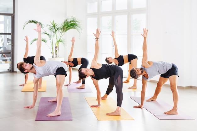 Grupa młodych sportowców wykonujących pozy obrotowy trójkąt lub parivrtta trikonasana, ćwicząc jogę na matach w jasnym, przestronnym studio