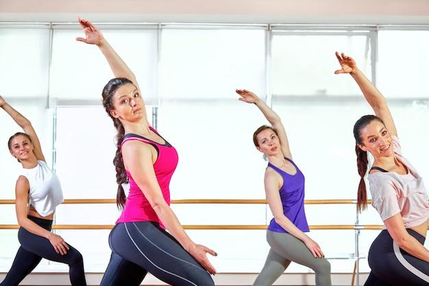 Grupa młodych sportowo atrakcyjnych ludzi praktykujących lekcję jogi z instruktorem