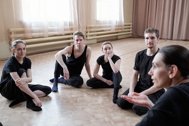 Grupa młodych, sprawnych mężczyzn i kobiet w czarnej odzieży sportowej siedzi na podłodze i słucha instruktora tańca w studio