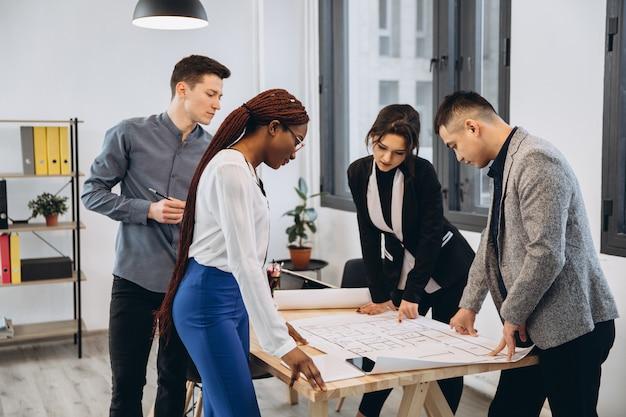 Grupa młodych studentów płci męskiej i żeńskiej dzielących się pomysłami podczas pracy nad projektem poprawiania błędów w rysunkach architektonicznych bez korzystania z technologii współpracujących w przestrzeni coworkingowej z biurem ofert
