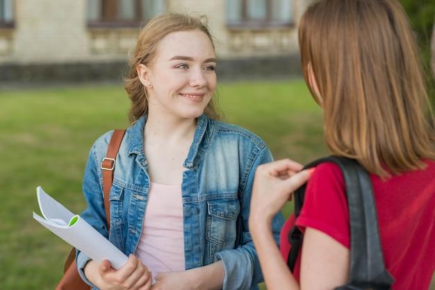 Grupa młodych studentów przed budynkiem szkoły
