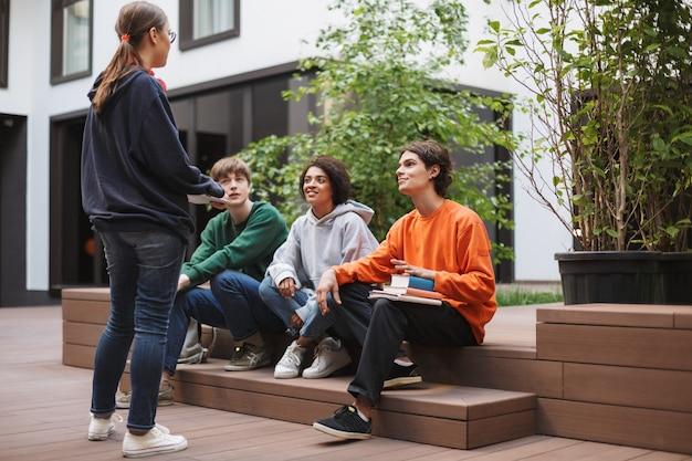 Grupa młodych studentów siedzi i przygotowuje się do lekcji podczas wspólnej nauki na dziedzińcu uniwersytetu