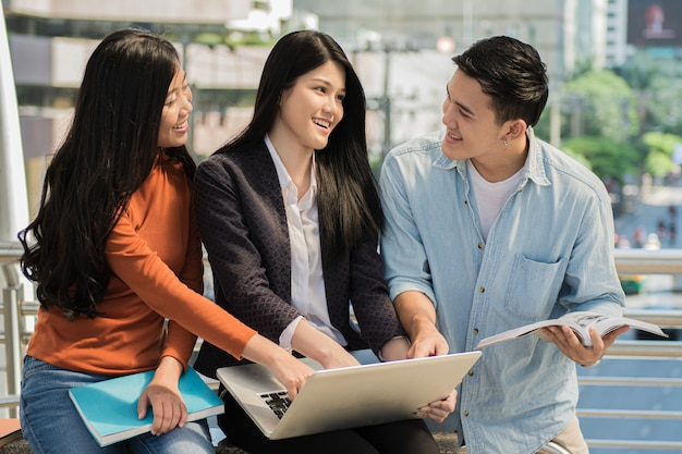 Grupa młodych studentów studiujących i czytających razem w sali uniwersyteckiej podczas przerwy z książkami i laptopem