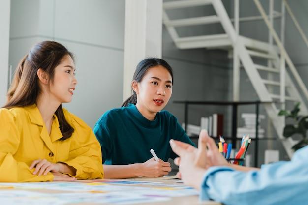 Grupa młodych studentów w eleganckim casual na kampusie. przyjaciele burza mózgów spotkanie rozmawia i omawia pomysły na pracę nowy projekt w nowoczesnym biurze. praca zespołowa współpracownika, koncepcja uruchomienia.