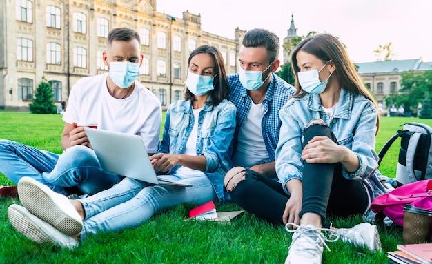 Grupa młodych studentów w maskach medycznych z laptopem i książkami studiuje razem na uniwersytecie. znajomi na zewnątrz siedzi na trawie.