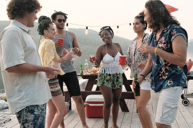 Grupa młodych szczęśliwych ludzi tańczących razem i picia alkoholu podczas imprezy na świeżym powietrzu