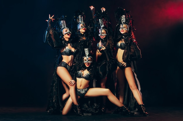 Grupa młodych szczęśliwych uśmiechniętych pięknych tancerek w karnawałowych sukienkach pozujących na czarnym tle studyjnym