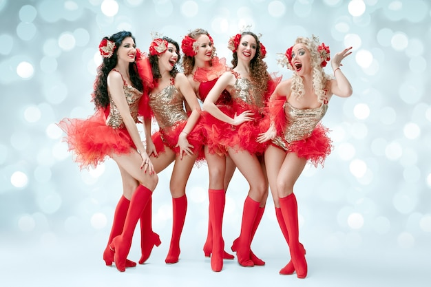 Grupa młodych szczęśliwych uśmiechniętych pięknych tancerek w karnawałowych sukienkach pozujących na niebieskim tle studyjnym