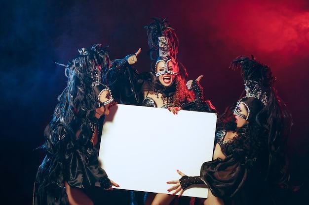 Grupa młodych szczęśliwych uśmiechniętych pięknych tancerek w karnawałowych sukienkach pozujących z pustym plakatem na czarnym tle studyjnym