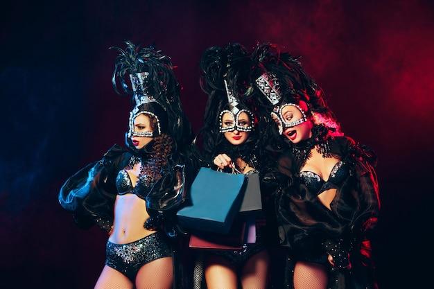 Grupa młodych szczęśliwych uśmiechniętych pięknych tancerek w karnawałowych sukienkach pozujących z torbami na zakupy na czarnym tle studyjnym