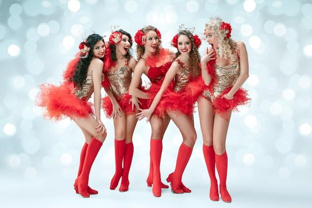 Grupa młodych, szczęśliwych uśmiechniętych pięknych tancerek w karnawałowych sukienkach