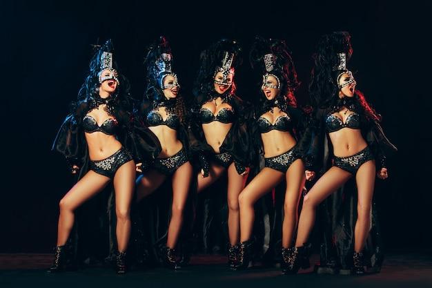 Grupa młodych, szczęśliwych uśmiechniętych pięknych tancerek w karnawałowych sukniach pozujących