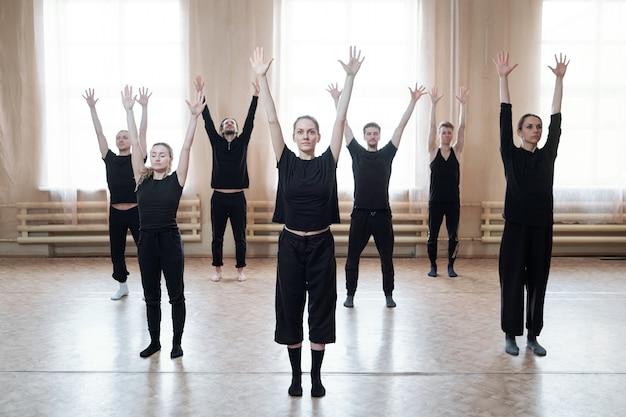 Grupa młodych tancerzy w czarnej odzieży sportowej podnosząc ręce stojąc na podłodze naprzeciw okna w studio tańca nowoczesnego