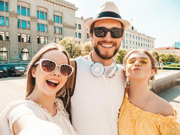 Grupa młodych trzech stylowych przyjaciół na ulicy. mężczyzna i dwie śliczne dziewczyny ubrane w letnie ubrania. uśmiechnięte modele bawiące się w okularach przeciwsłonecznych. kobiety i facet robiące selfie na smartfonie