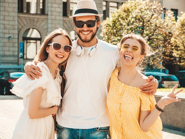 Grupa młodych trzech stylowych przyjaciół pozowanie na ulicy. moda mężczyzna i dwie słodkie dziewczyny ubrane w letnie ubrania. uśmiechnięte modele zabawy w okularach przeciwsłonecznych. wspaniałe kobiety i facet wariują