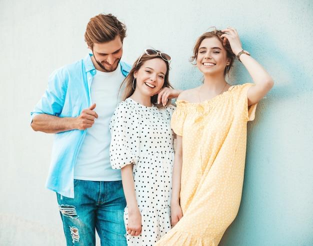 Grupa młodych trzech stylowych przyjaciół pozowanie na ulicy. moda mężczyzna i dwie słodkie dziewczyny ubrane w letnie ubrania. uśmiechnięte modele zabawy w pobliżu ściany. wspaniałe kobiety i facet na zewnątrz