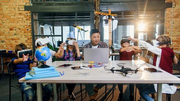 Grupa młodych uczniów szkoły podstawowej korzystających z okularów rzeczywistości wirtualnej podczas zajęć z kodowania komputerowego.
