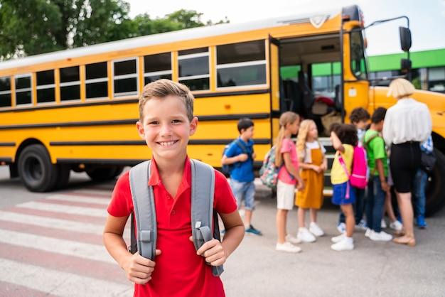 Grupa młodych uczniów uczęszczających do szkoły podstawowej w żółtym autobusie szkolnym - dzieci ze szkoły podstawowej bawią się