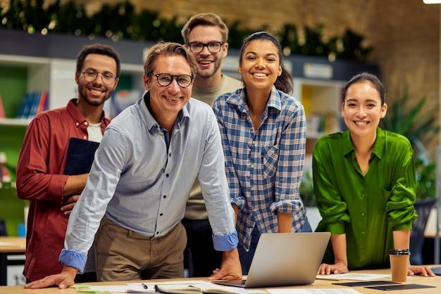 Grupa młodych udanych wieloetnicznych zespołów biznesowych patrzących na kamerę i uśmiechających się podczas posiadania