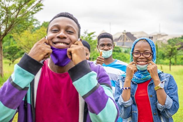 Grupa młodych wesołych afrykańskich przyjaciół noszących maski na twarzach i dystansujących się w parku