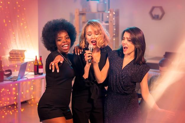 Grupa młodych wesołych kobiet w czarnych sukienkach stojących przed kamerą i śpiewających razem karaoke na imprezie domowej