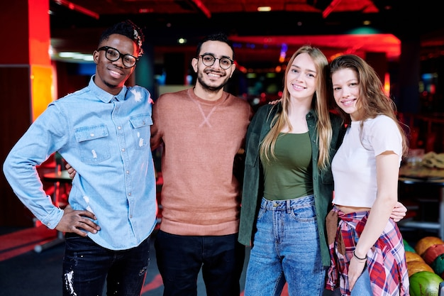 Grupa młodych wesołych przyjaciół międzykulturowych stojących w rzędzie w objęciach na tle kręgielni w centrum rozrywki