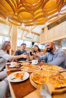 Grupa młodych wesołych przyjaciół siedzi w kawiarni rozmawiając i jedząc pizzę. obiad w pizzerii.