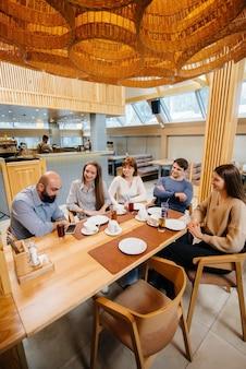 Grupa młodych wesołych przyjaciół siedzi w kawiarni rozmawiając i jedząc pizzę