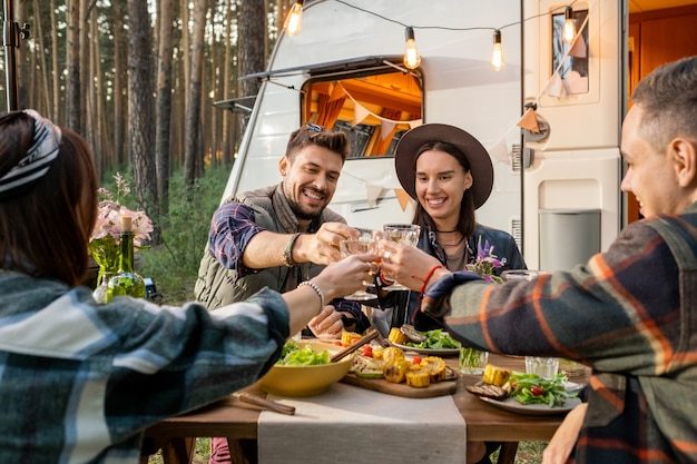 Grupa młodych wesołych przyjaciół wznoszących tosty z winem