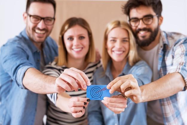 Grupa młodych wesołych szczęśliwych ludzi trzymających niebieską naklejkę wraz z obrazem clipart strzałki i celu.