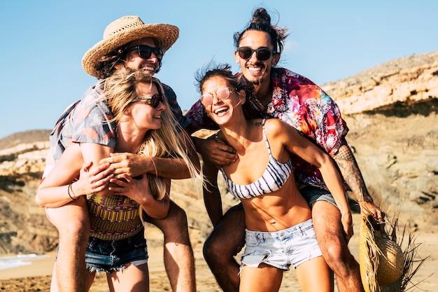 Grupa młodych wesołych szczęśliwych pokoleń milenialsów spędzających wolny czas na świeżym powietrzu, bawiących się razem jak przyjaciele i dobrze się bawiąc, śmiejąc się i uśmiechając w słoneczny dzień na łonie natury na plaży