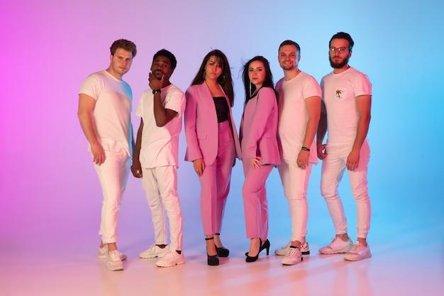 Grupa młodych, wieloetnicznych muzyków stworzyła zespół, pozujący w neonowym świetle na gradientowym tle