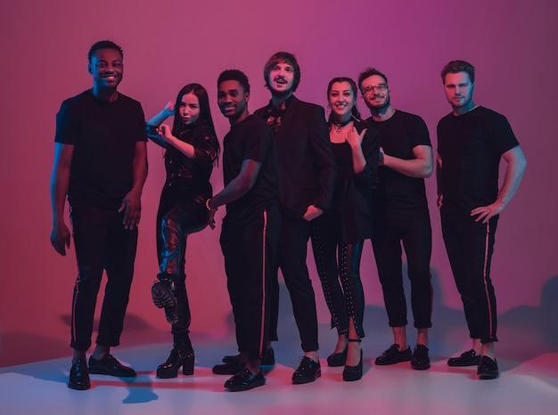 Grupa młodych, wieloetnicznych muzyków stworzyła zespół, tańczący w neonowym świetle na różowym tle. pojęcie muzyki, hobby, festiwalu, odnowy biologicznej. radosny gospodarz imprezy, tancerz, wokalista, gitarzysta, saksofonista.