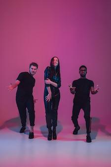 Grupa młodych wieloetnicznych muzyków stworzyła zespół tańczący w neonowym świetle na różowym tle