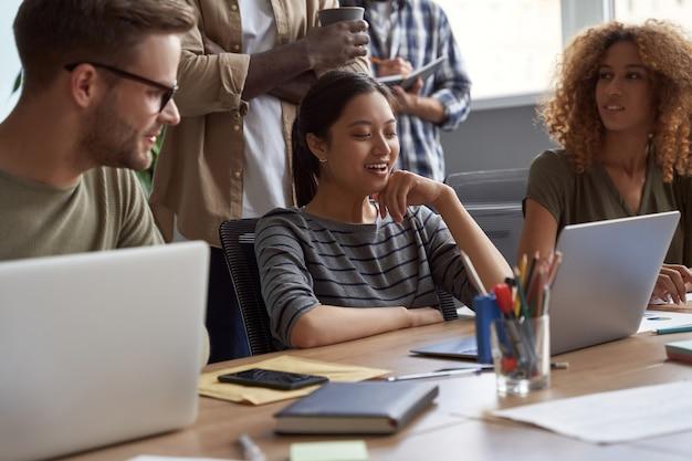 Grupa młodych, wielokulturowych ludzi biznesu pracujących razem w nowoczesnym, odnoszącym sukcesy zespole biurowym