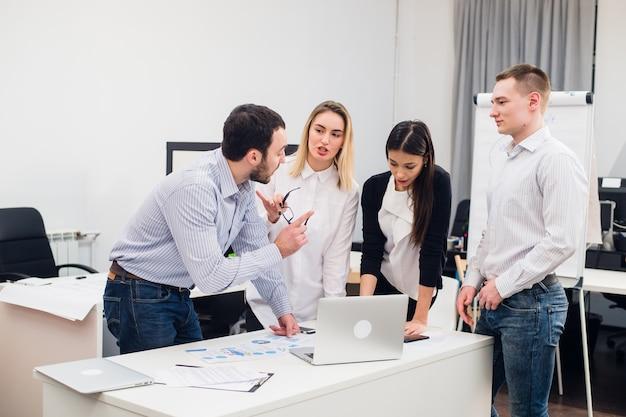 Grupa młodych współpracowników podejmujących świetne decyzje biznesowe. kreatywna dyskusja zespołu koncepcja pracy korporacyjnej nowoczesne biuro. prezentacja pomysłu na marketing startowy.