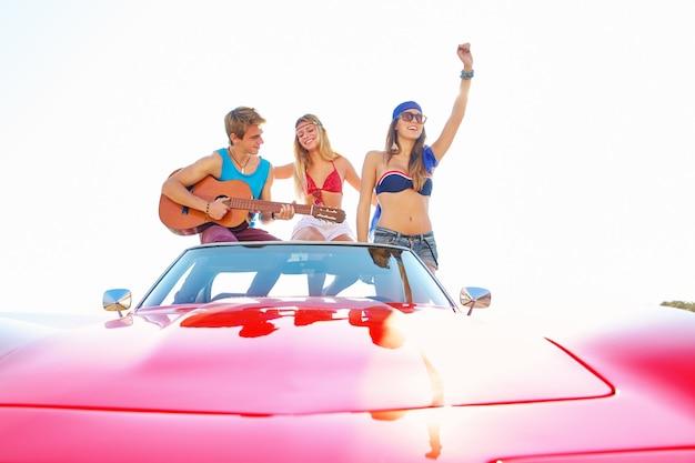 Grupa młodych zabawę na plaży gra na gitarze