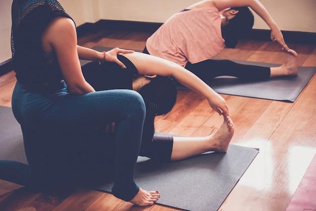 Grupa młodych zdrowych azjatyckich kobiet praktykujących lekcję jogi z instruktorem w domowym studio, praca w domu.