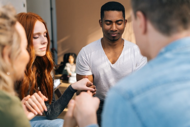 Grupa młodych, zróżnicowanych, wieloetnicznych ludzi trzymających się za ręce podczas psychoterapii, medytujących i wspólnie rozwiązujących problemy psychiczne. koncepcja grupowego doradztwa problemów zdrowia psychicznego