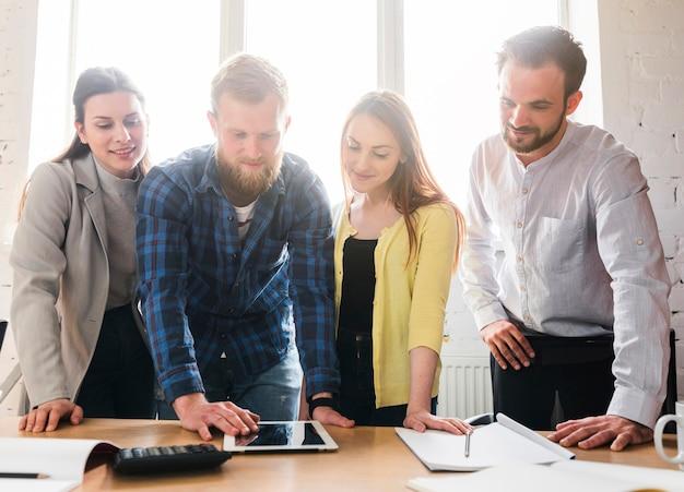 Grupa młodzi biznesmeni patrzeje cyfrową pastylkę na biurku w biurze