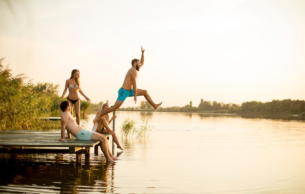 Grupa młodzi ludzie ma zabawę na molu przy jeziorem