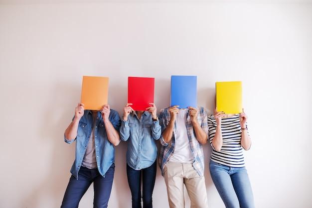 Grupa młodzi ludzie zakrywa twarze z falcówką podczas gdy stojący przeciw biel ścianie. uruchomienie koncepcji biznesowej.