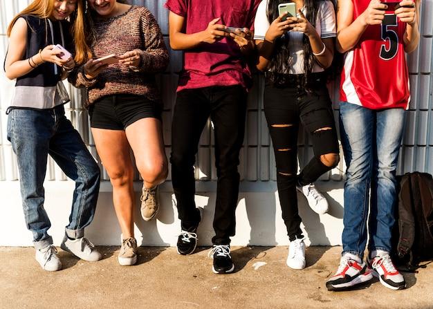 Grupa młodzi nastolatków przyjaciele chłodzi out wpólnie używać smartphone ogólnospołecznego medialnego pojęcie
