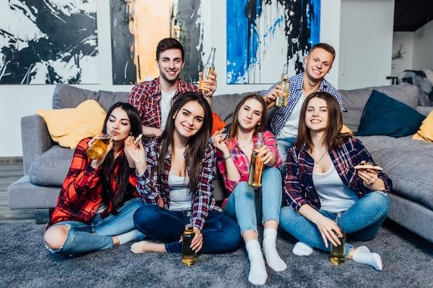 Grupa młodzi rozochoceni przyjaciele ma zabawę podczas gdy pijący piwo w domu.