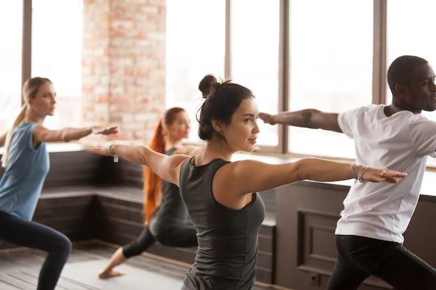 Grupa młodzi sporty ludzie stoi w wojownika dwa ćwiczeniu