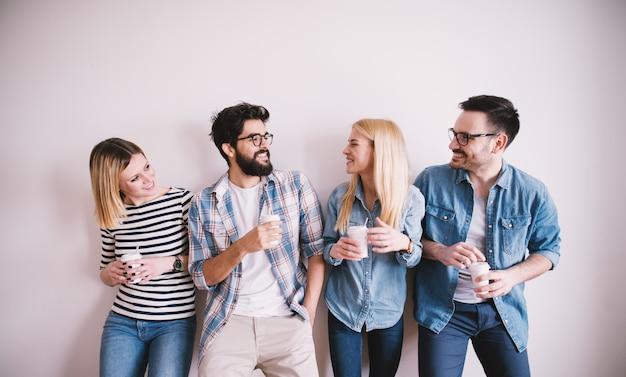 Grupa młodzi stylowi szczęśliwi ludzie opiera o ścianę i opowiada podczas gdy pije kawę w papierowej filiżance.
