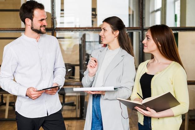 Grupa młodzi uśmiechnięci biznesmeni dyskutuje projekt przy biurem
